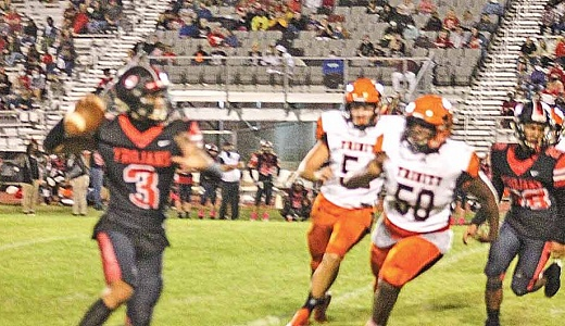 Coldspring-Oakhurst quarterback Duke Lawniczak (3) rolls out as he looks for an open wide receiver during the Trojans' 48-8 rout of Trinity last Friday. (Photo by Scott Womack)